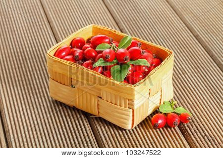 Fresh rosehip fruit and leaves in a basket.