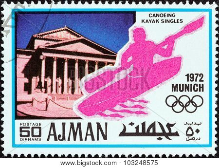 AJMAN EMIRATE - CIRCA 1972: Stamp shows the National Theatre and canoeing kayak singles