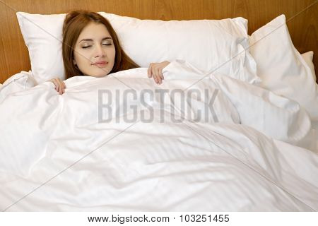 Portrait of a beautiful young adult attractive sexy and sensuality pretty brunette woman sleeping in a bed in the bedroom