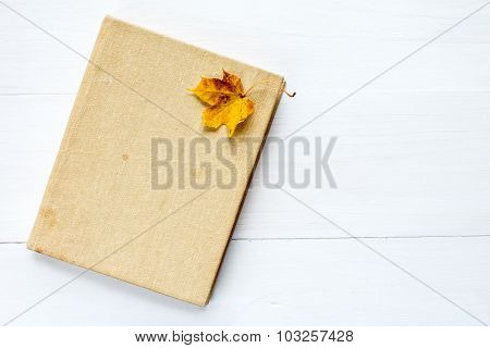 Book And Old Leaf On Wooden Background