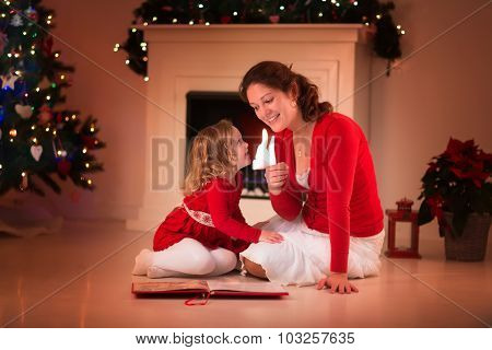 Mother And Daughter Reading At Fire Place On Christmas Eve
