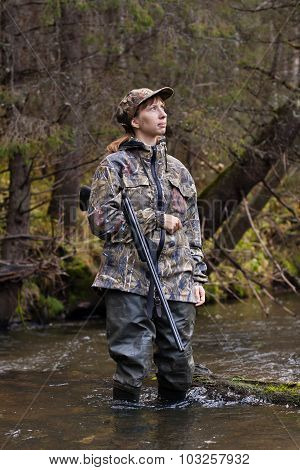 Woman Hunter In Camouflage On The River