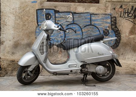 VALENCIA, SPAIN - SEPTEMBER 28, 2015: A silver Vespa scooter parked near the town center of Valencia. Vespa is an Italian brand of scooter manufactured by Piaggio.
