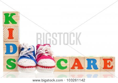 Kids Care words formed by wood alphabet blocks and booties, isolated on white background