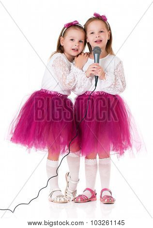 Beautiful little twins girls with microphone isolated on white background