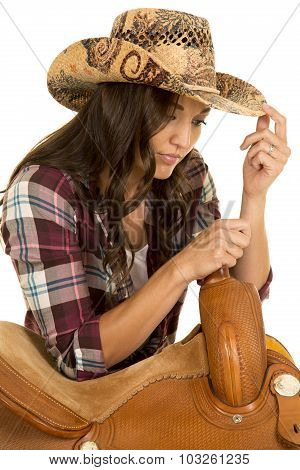 Cowgirl In Plaid Shirt And Hat Lean On Saddle Look Down