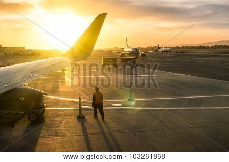 Working Man Walking Near Airplane Wing At The Terminal Gate Of International Airport During Sunset