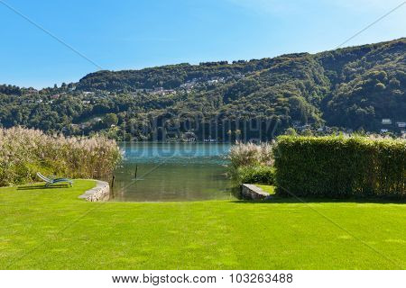 park of a property on the lake, two sunbeds