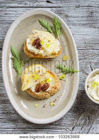 Bruschetta With Cheese, Pear, Honey And Nuts On The Oval Plate On A Light Wooden Surface