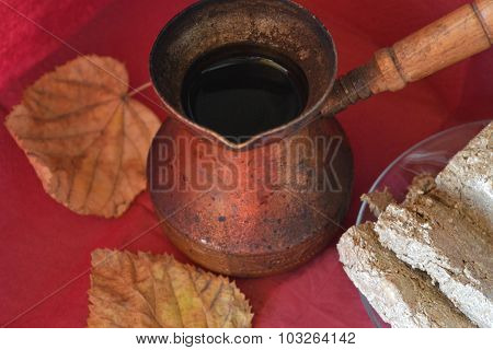 Old copper Turkish coffee pots, Middle Eastern sweets and yellow autumn leaf on burgundy surface