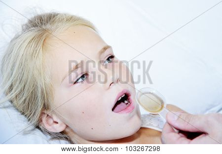 Sick Girl Taking Medicine From A Spoon Laying In Bed