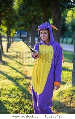 Girl wearing a carnival costume of dragon taking selfie