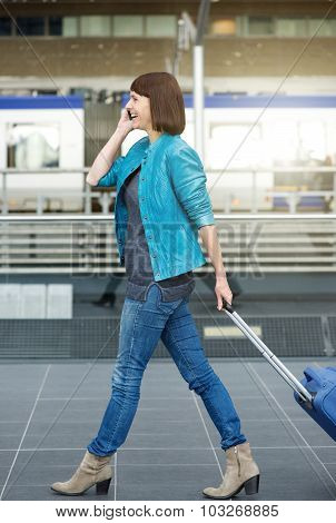 Traveling Woman Walking With Suitcase And Mobile Phone At Airport
