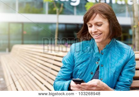 Smiling Mature Woman Using Mobile Phone Outside