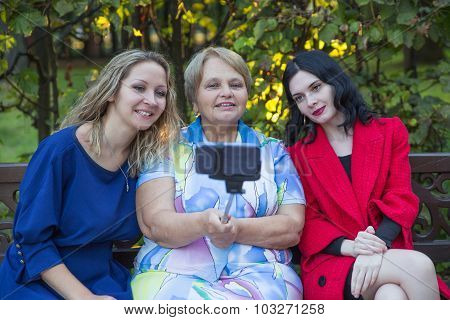 Two daughter with old mother taking selfie by phone with monopod