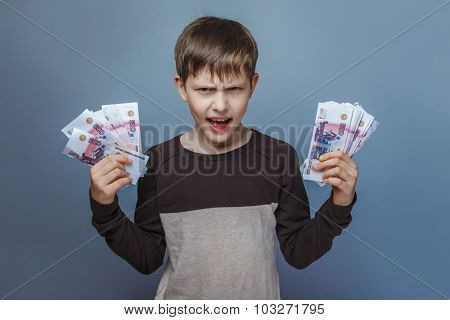Boy  teenager European appearance ten years holding a wad of mon