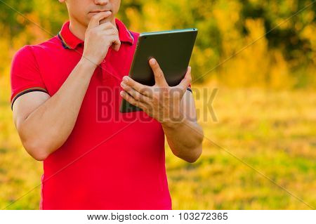 Businessman In A Park Holding A Touch Screen Device