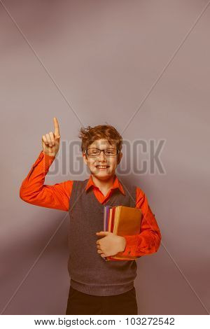 European-looking  boy of ten  years in glasses thumbs up, the id