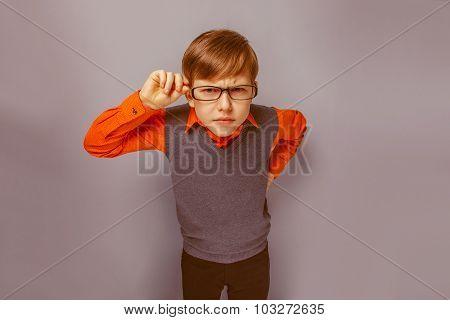 European-looking  boy of ten years in  glasses  frowning, unhapp