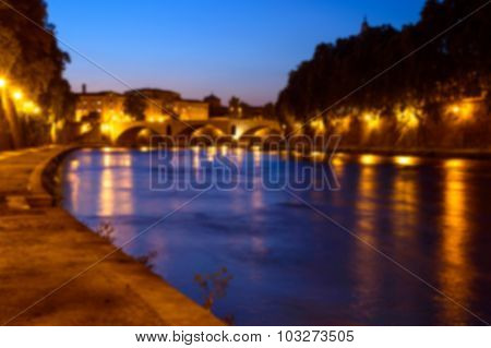 Artistic Blur Background Of Rome Cityscape At Night, On The River Tiber