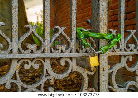 Old Rusty Metal Gate With A Chain Lock