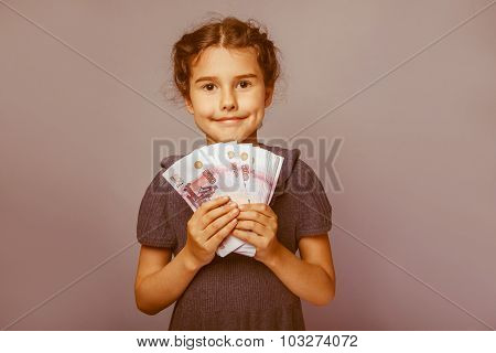 girl child European appearance ten years  holding a wad of money
