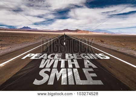 Peace Begins With a Smile written on desert road