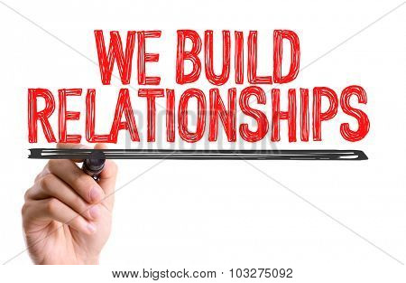 Hand with marker writing: We Build Relationships