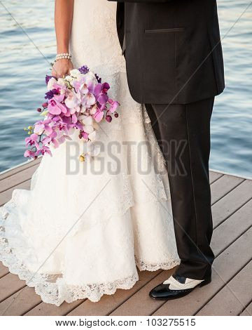 bride and groom purple bouquet, black and white spats on the lake dock