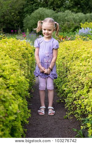 Little Girl With Pigtails On Footpath In The Corridor Of The Bushes