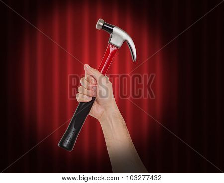 Hand holding a hammer in the spot light