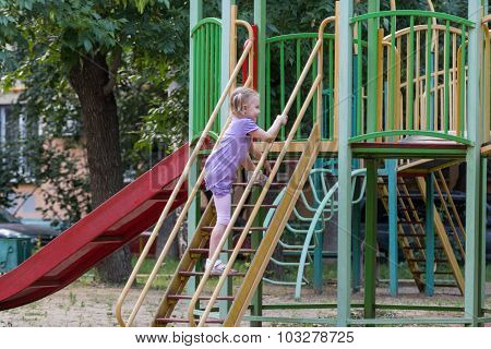 Little Girl With A Ponytail Climbs The Stairs To The Slide