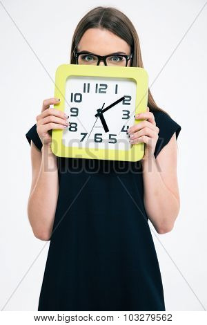 Portrait of a young woman covering her face with big clock isolated on a white background