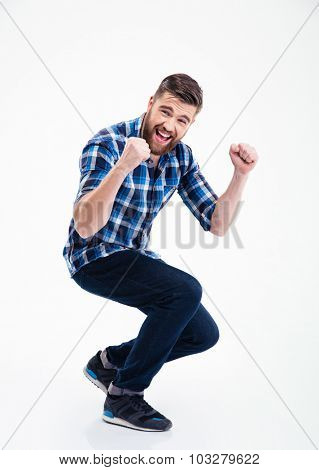 Full length portrait of a happy casual man celebrating his success isolated on a white background