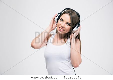 Portrait of a smiling cute girl listening the music in headphones isolated on a white background
