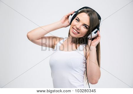 Portrait of a happy pretty girl listening the music in headphones isolated on a white background