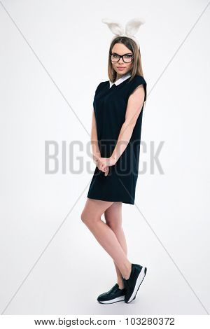 Full length portrait of a beautiful woman with rabbit ears standing isolated on a white background