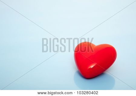 Single red heart on blue background
