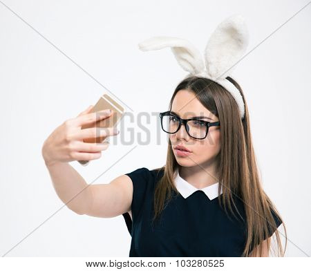 Portrait of a beautiful woman with bunny ears making selfie photo on smartphone isolated on a white background