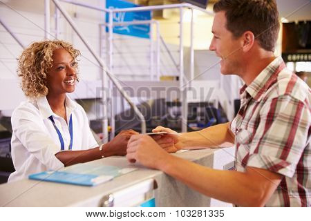 Staff At Airport Check In Desk Handing Ticket To Passenger