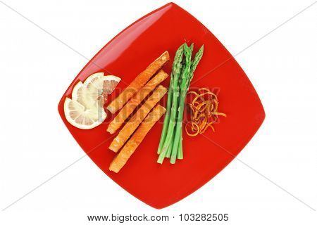 grilled salmon slices with asparagus lemon and fried orange peel on red plate isolated over white background