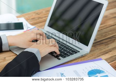 Closeup of business woman hand typing on laptop keyboard