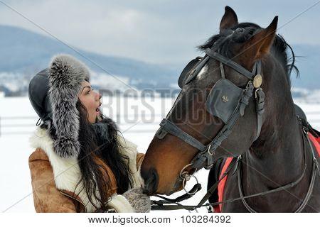 beautiful brunette woman portrait with horse in winter