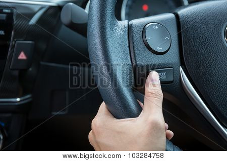 A Woman Hand Pushes The Mode Hold Control Button On A Steering Wheel.