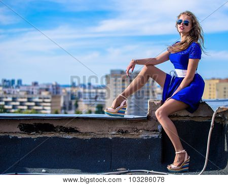 young woman in blue dress on roof top whole length