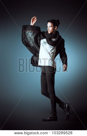 Fashion shot of a handsome male model in black suit posing in motion over gray background. Men's beauty.
