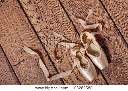 Ballet Pointe Shoes Lie On Wooden Floor.