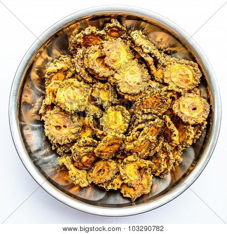 Tasty fried bittergourd chips kept on a stainless steel container on a plain background