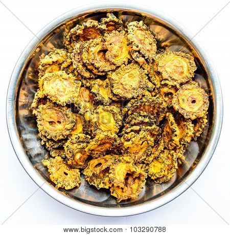 Bittergourd chips kept on a glass bowl on a plain background