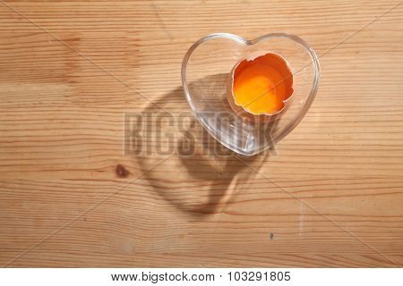 Brown eggs in heart shape transparent bowl on wooden background.